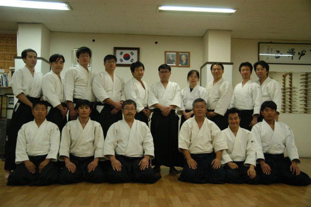 A student reunion with Homma Kancho and Yoon Sensei.  The center spot is left open as a symbol of respect for presiding Shihan.