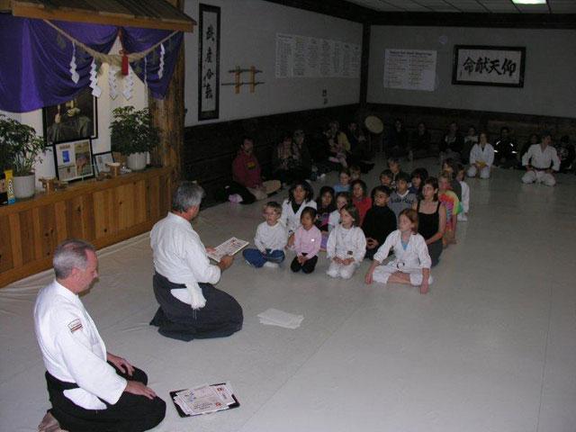 Noel Camp Sensei presenting promotion certificates to children