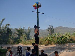Climbing oiled bamboo poles