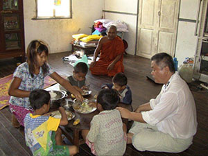 Miss May serving meals to the children and Homma Kancho