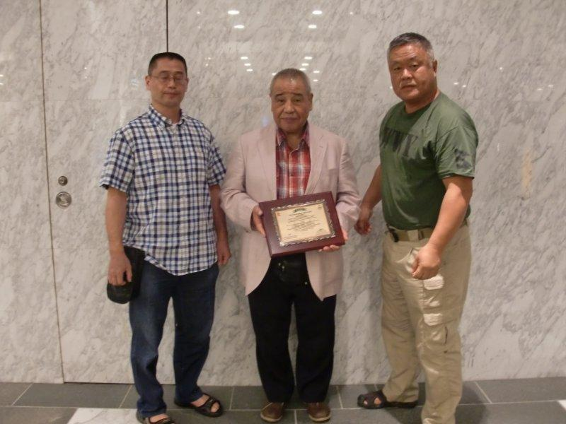 On return trip from Nepal- Homma Kancho presents Appreciation Plaque from the Nepal Army Rangers to Kobayashi Soshihan in Japan. Center: Kobayashi Soshihan- Left: Hiroaki Kobayashi Dojocho
